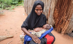 A mother holds her newborn baby, who suffered from an umbilical cord infection, in Makoror, Kenya.