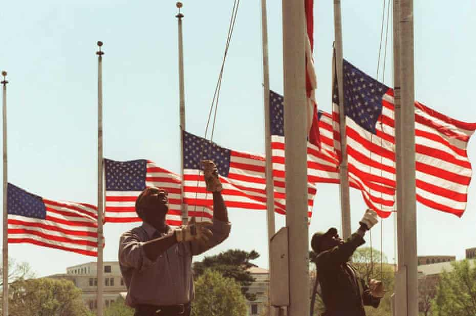 Two US Park Service employees lower the 50 flags surrounding the Washington Monument on 20 April 1995.