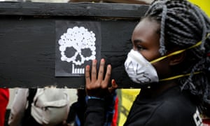 A campaigner carries a coffin during a protest against the construction of a coal plant in Lamu on Kenya's coast, in Nairobi on June 12, 2019.