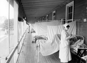 A nurse checking on a patient at the Walter Reed hospital flu ward during the influenza pandemic in 1918.
