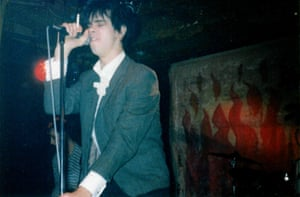 A young Nick Cave sings on stage with a cigarette in his hand