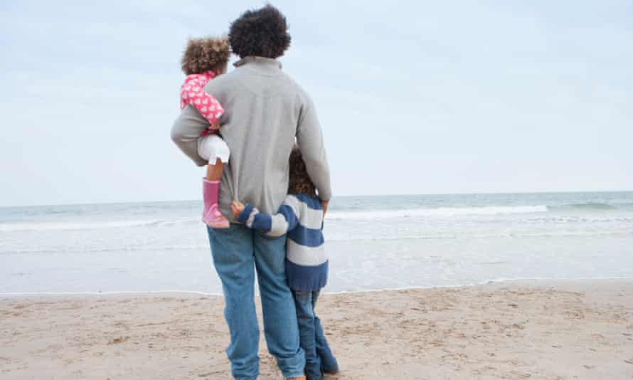 Father Hugging Children On Winter Beach
