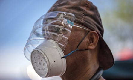 A man is seen wearing a makeshift mask made out of a styrofoam cup and a face shield made out of a plastic bottle to protect against Covid-19 in Manila