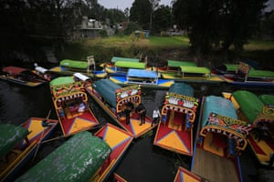 "Mexico city, MexicoBoats come in to dock amidst parked ""trajineras,"" the colorful passenger vessels typically rented by tourists and families in Xochimilco."