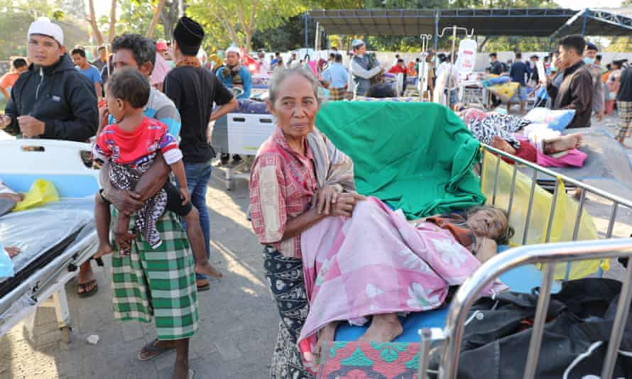People wait for treatment outside a hospital in northern Lombok