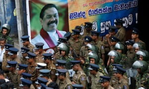 Sri Lankan police and special forces stand guard next to a poster of the newly appointed prime minister, Mahinda Rajapaksa, in Colombo