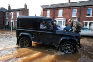 Soldiers help Margaret McCraken, 79, from her home in Broad Street, Carlisle, during flooding in December 2015