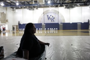 Mary Lewis, an evacuee from the Tick fire, sits on a cot at a shelter inside the West Ranch high school gym in Santa Clarita.