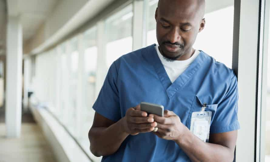 A doctor is seen using a phone