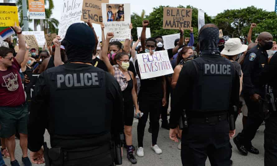 Protesters are confronted by police officers as they demonstrate peacefully for George Floyd on 7 June.