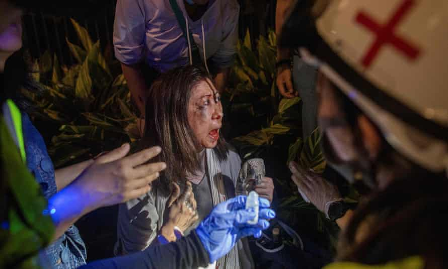 A woman who was beaten after removing anti-government posters is treated by medics.