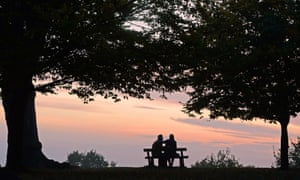 A couple sits on a bench.