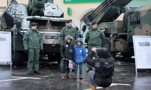 Children pose for photos with members of the Polish army.