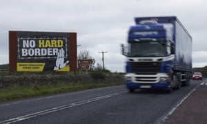 A truck races past a sign against the reestablishment of a hard border between Northern Ireland and the Republic of Ireland