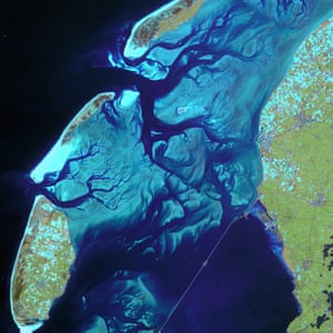 This satellite image shows the ever-moving sandbanks in the shallow Wadden Sea in the north of the Netherlands. This unique region is one of the largest wetlands in the world. As this satellite image shows, the sandbanks are bordered by relatively deep channels and gullies, which provide a route for boats crossing between the islands and mainland.
