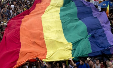 People carry a giant rainbow flag during the annual Gay Pride Parade along Copacabana beach in Rio de Janeiro, Brazil, Sunday, Sept. 30, 2018.