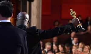Barry Jenkins with his Oscar for best picture. In the foreground is La La Land's director, Damien Chazelle.