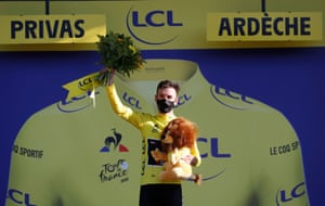 Mitchelton-Scott rider Adam Yates, wearing the overall leader's yellow jersey, celebrates on the podium.