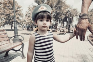 A little girl holds her father's hand during paratroopers day in Donetsk