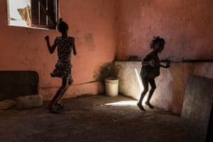 Fatdjoulie, seven, and Jean Gous Emenco, 11, dance in an empty room under their one-bedroom house