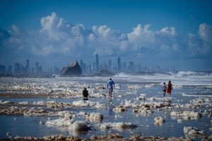 Tourists walk amongst beach foam in the wake of cyclonic conditions at Currumbin beach.