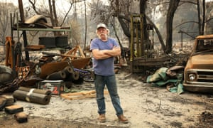 A resident of Glen Ellen, a small town in northern California, poses for a portrait on his fire damaged property.