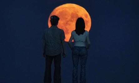 Last year's Harvest Moon, rises behind Sean Henry's sculpture the Couple at Newbiggin-by-the-Sea in Northumberland.
