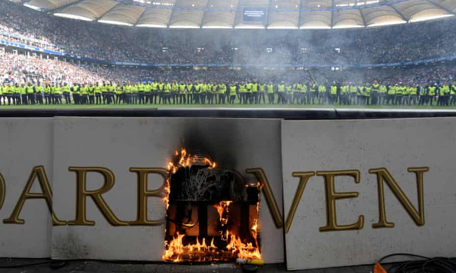 An advertising hoarding on fire as stewards are lined up across the pitch after trouble marred Hamburg's relegation.