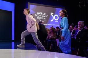 Swedish climate activist Greta Thunberg (L) accompanied by Zambian activist Natasha Mwansa arrives at the event