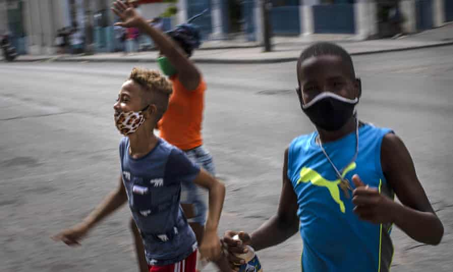 Children wearing masks as a precaution amid the spread of the new coronavirus run across a street in Havana.