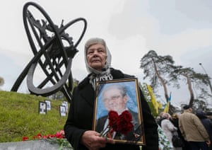 A woman holds a portrait of her husband near a monument honoring people who were killed during cleanup efforts after the Chernobyl nuclear power plant disaster, during a memorial ceremony in Kiev