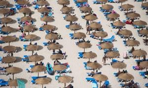 Sun umbrellas on Cala en Porter beach in Menorca, Spain
