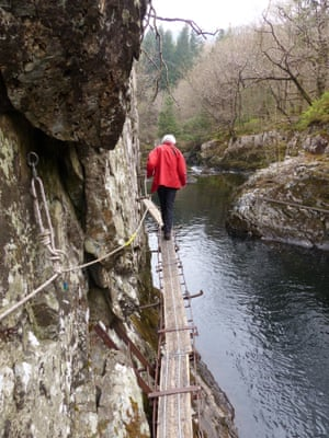 A man on the walkway high above the river