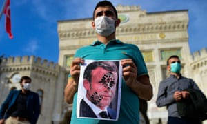 A protester in Istanbul holds a picture of Emmanuel Macron, which has been defaced with a shoe print