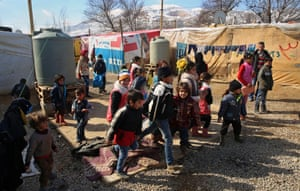 Children leave a makeshift school at the end of lessons at a camp in the Bekaa