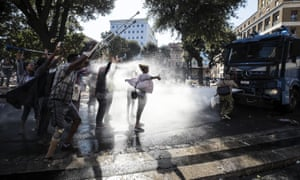 Italian law enforcement use water cannon to disrupt a protest after police evicted Eritrean and Ethiopian migrants from a building they had occupied since 2013.