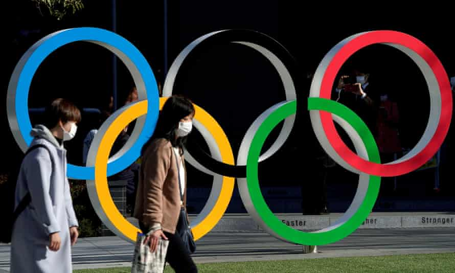 Women wearing protective face masks walk past the Olympic rings in Tokyo.