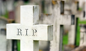 A cross in a graveyard with the letters RIP