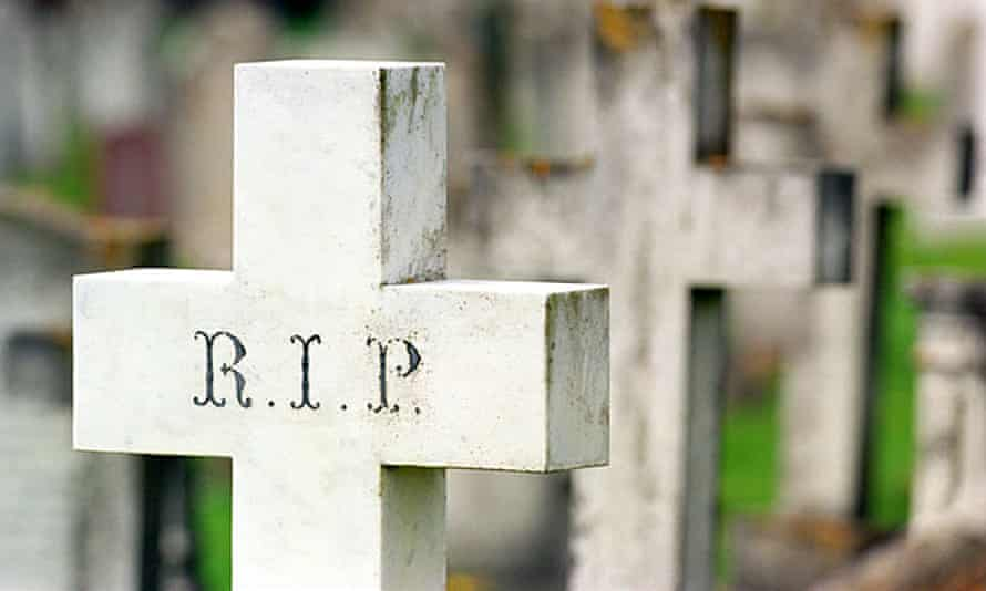A cross in a graveyard saying RIP