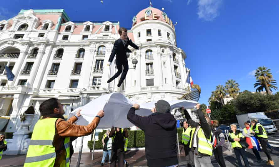An effigy of Emmanuel Macron is thrown into a sheet during a gilets jaunes protest in Nice.