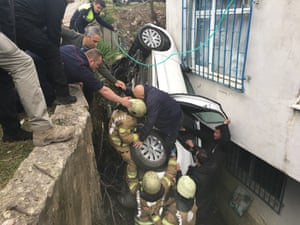 Firefighters help a man out of a car