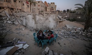 Rafah, Gaza. Palestinians enjoy iftar, the evening meal with which Muslims end their daily Ramadan fast, near the rubble of a residential building destroyed by Israeli warplanes.