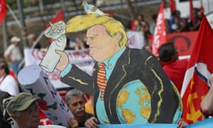 Demonstrators, including one carrying a coardboard effigy of US president Donald Trump, march to protest the G7 summit on 27 May 2017 in Giardini Naxos, Italy