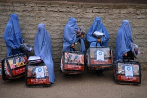 Herat, Afghanistan Women stand with aid items received from a charity