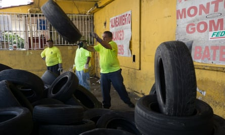 Employees with the municipal government collect used tires on 7 August 2016 in the Rio Piedras section of San Juan, Puerto Rico.