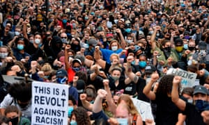 Protesters take a knee and raise their fists in a moment of silence for George Floyd and other victims of police brutality after marching to the Boston Police Station in Boston, Massachusetts on 7 June 2020.