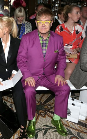 Elton John in the front row for Richard James spring/summer 13 collection in 2012, wearing a purple suit with green accessories.