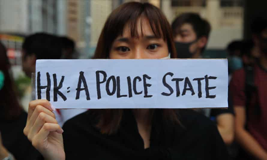 A woman holds a sign during a demonstration held to protest alleged abuse of pro-democracy protesters by Hong Kong police.