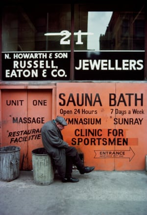 An elderly man sits on a dustbin outside a sauna and gymnasium in Manchester, 1977, from the exhibition The North by John Bulmer at Hull Central Library