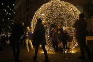 People take family photos in front of Christmas decoration in Athens, Greece.